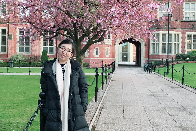 Yuan at our beautiful campus  in front of a cherry blossom tree