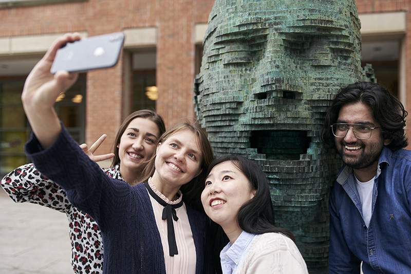 Yuan taking a selfie with friends outside the McClay library