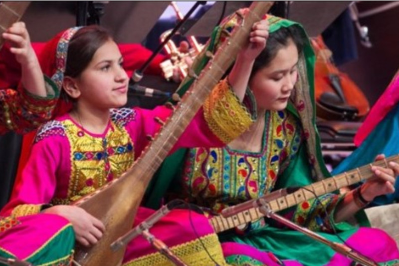 The image shows two young Afghan women in traditional clothing, playing stringed instruments as part of an Orchestra