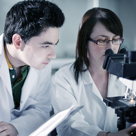 female student looking in to microscope with male student taking notes