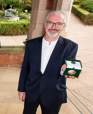 Richard English holding his medal