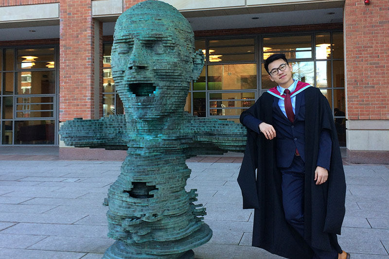 Rory Cao with the statue outside the McClay