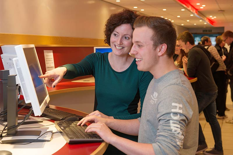 member of staff assisting student on a computer
