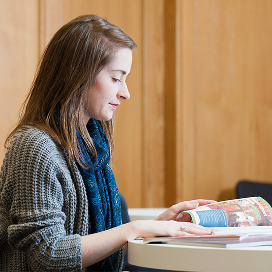 female student reading textbook in the McClay library
