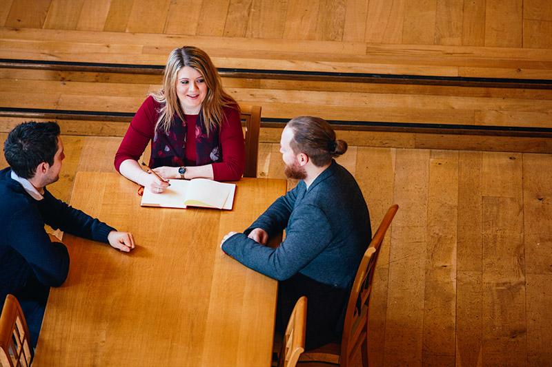high angle view of three students sitting at a desk having a conversation with one of them taking notes