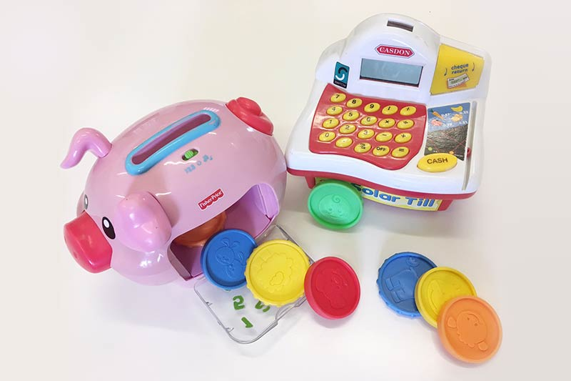 toy piggy bank with colourful plastic coins scattered beside it