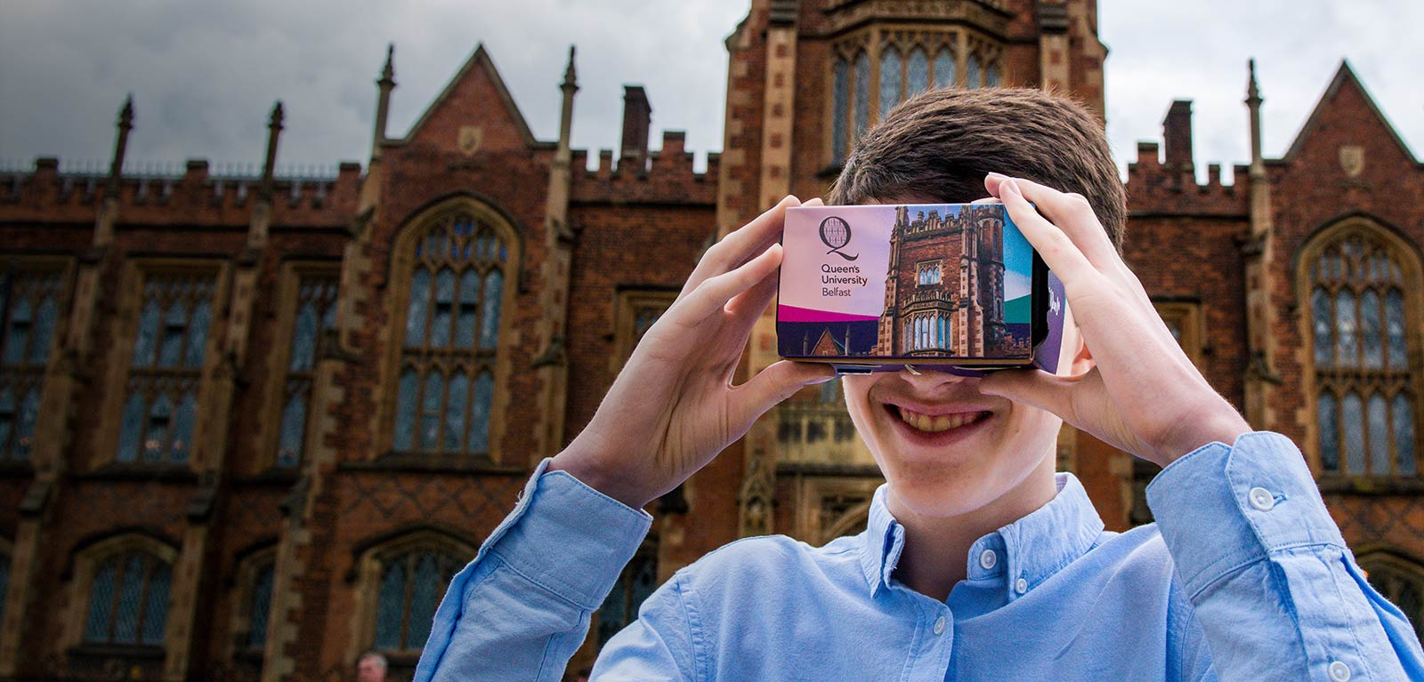 a student wearing a Queen's University Belfast Virtual Reality headset in front of the Lanyon building