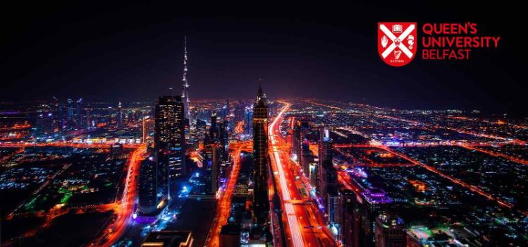 Brightly lit night image of Dubai cityscape with the Queen's logo