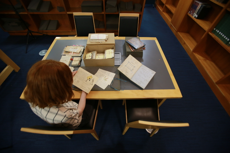 Staff member looking at Eva Price letters in Special Collections Reading Room.