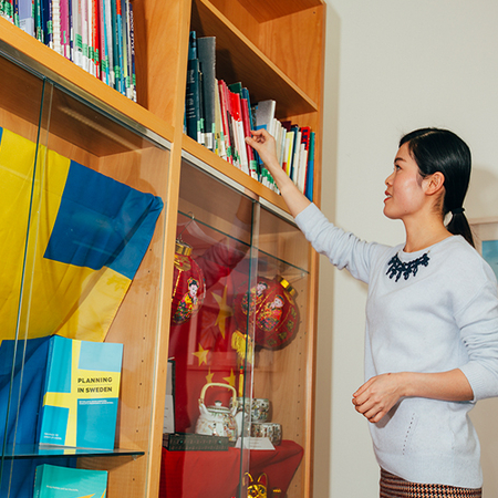 Student reaching for a book in the Language Centre