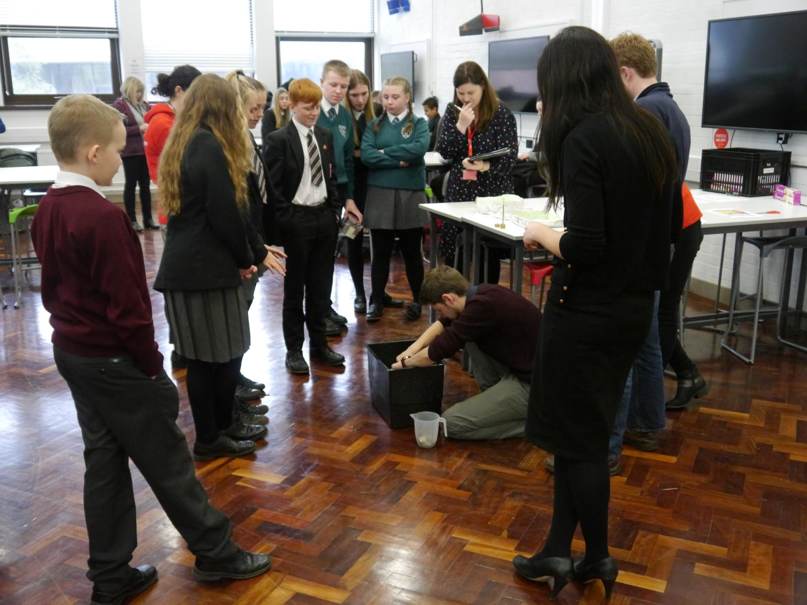 Year 10 pupils from different schools watch to see how much weight their tinfoil boats will hold in a mechanical engineering challenge.