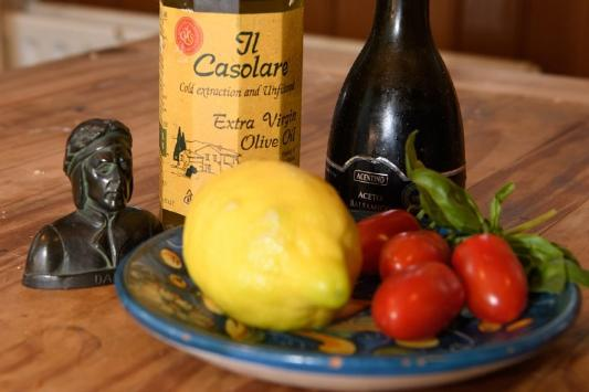 A bottle of Olive Oil, an Italian sculture and a plate of lemons and vine tomatoes on a wooden kitchen table