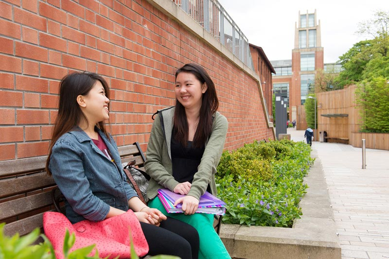 two international female students chatting on a bench outside the McClay library
