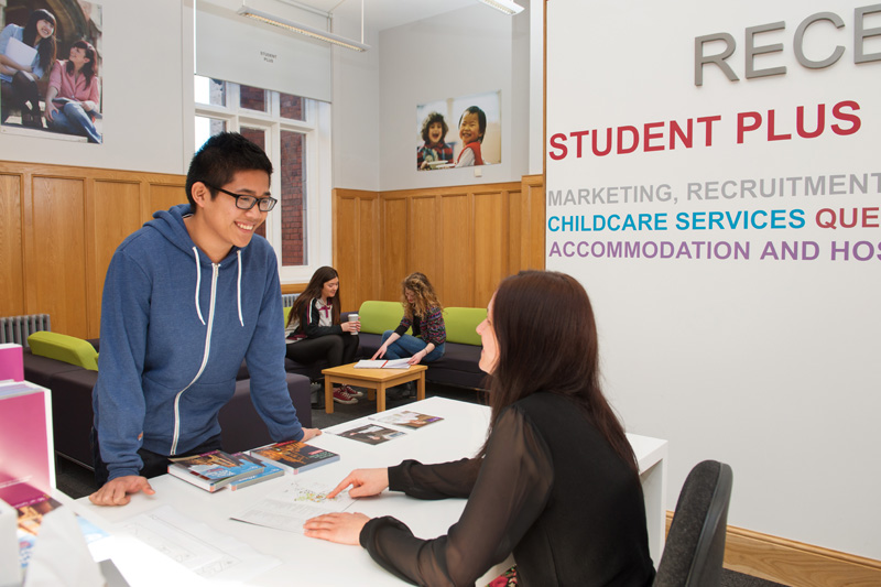 a male student chatting with a member of staff at the Student Plus reception desk