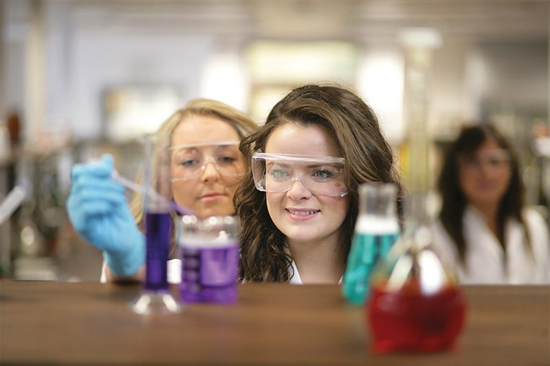female student in lab coat extracting a purple liquid from a beaker with a pipette