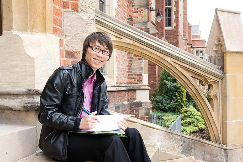 international student writing notes and sitting on the steps of lanyon south