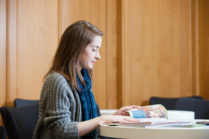 female student reading textbook