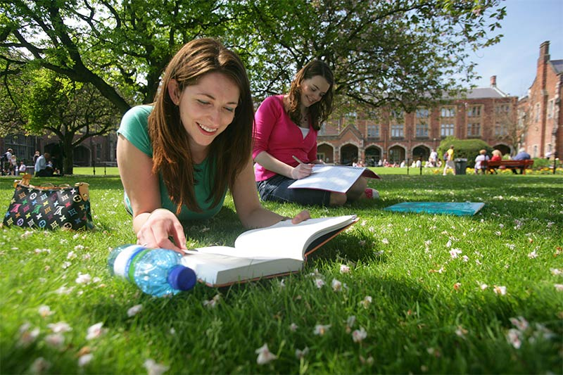 two female students studying on the grass in the Quad