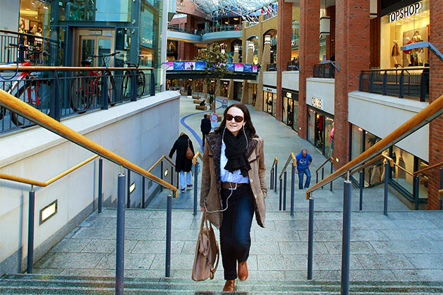 female student wearing sunglasses walking up the steps at Victoria Square Shopping Centre, Belfast