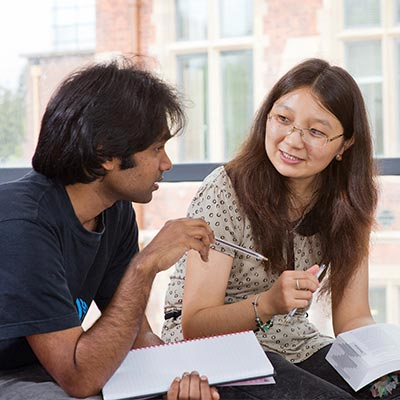 two international students discussing notes