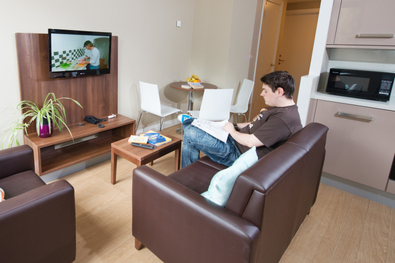 A male student looking at lecture notes in the living room of a Willow Walk student accommodation flat