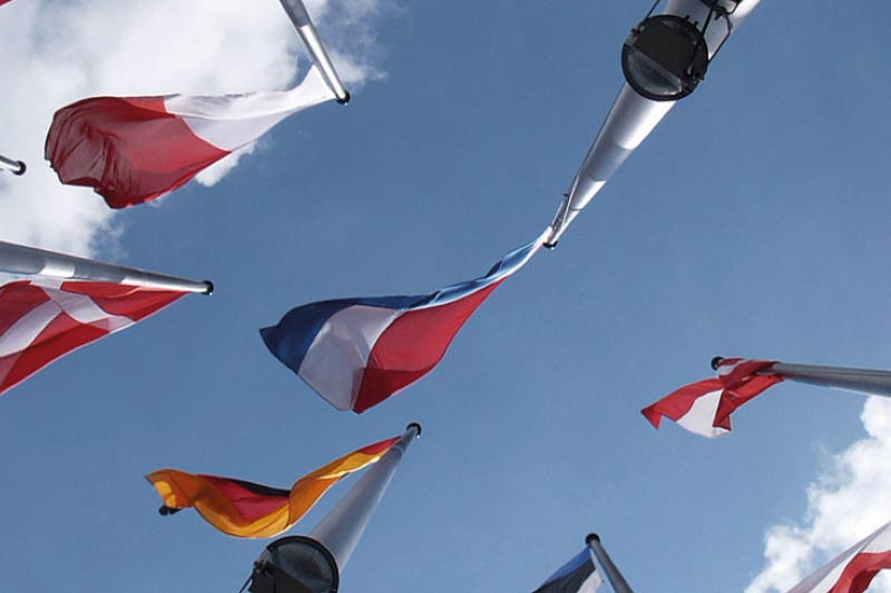 Multiple national flags flying beneath a blue sky