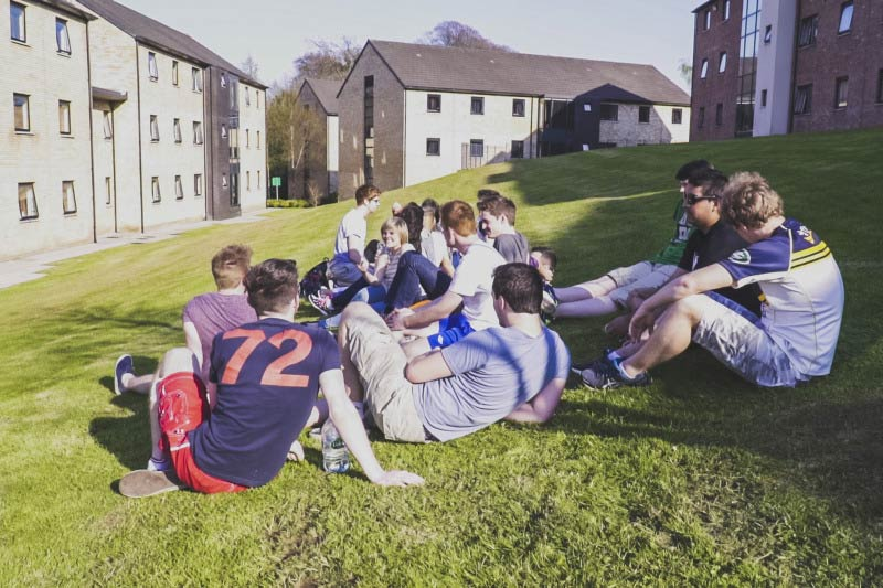 group of students sitting on grass in Elms village