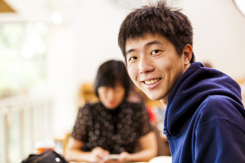 male Asian student wearing blue hooded jumper