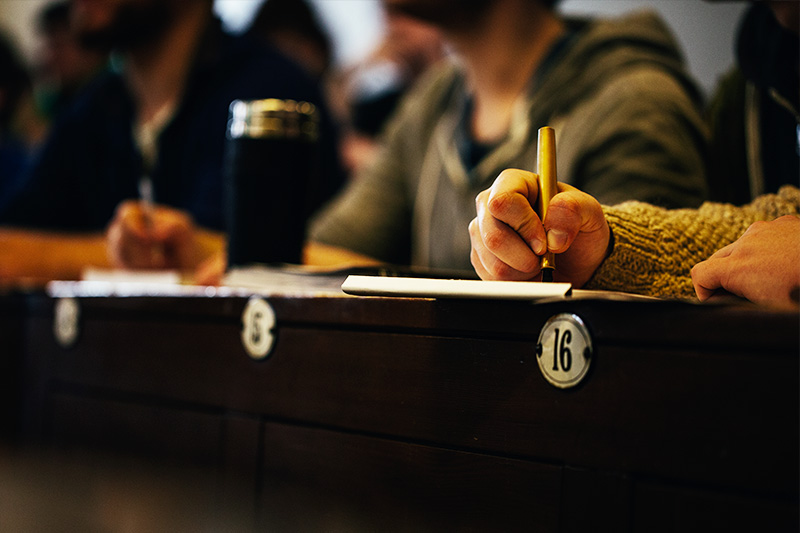 close up of a students hand taking notes on a notebook during a lecture with other students in the background