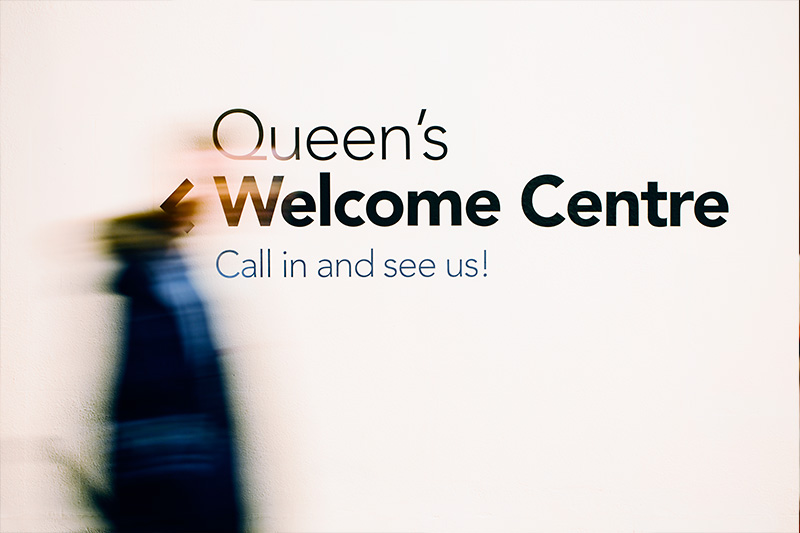 A silhouette of a student behind a frosted glass window with Queen's Welcome Centre graphic on it