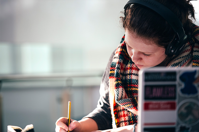 close up of a Female student wearing headphones and taking notes whilst using a laptop