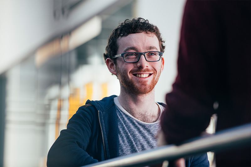 smiling male student wearing glasses facing someone with their back to camera