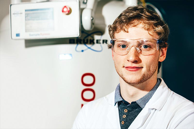 close up of ale postgraduate student in labratory wearing safety goggles and lab coat
