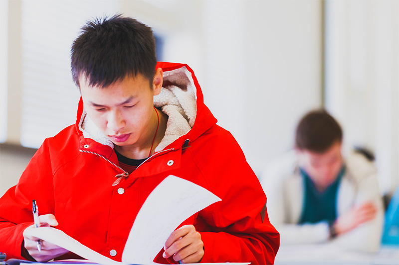 Student in red coat reading lecture notes