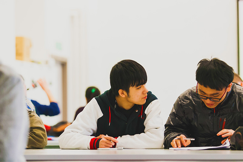 2 male students discussing their notes