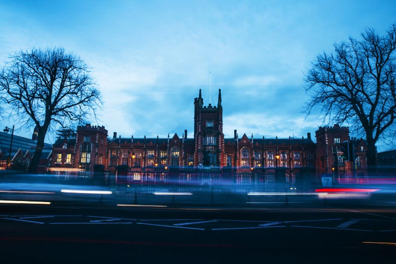 timelapse shot of Lanyon building at night time from across university road with cars in foreground
