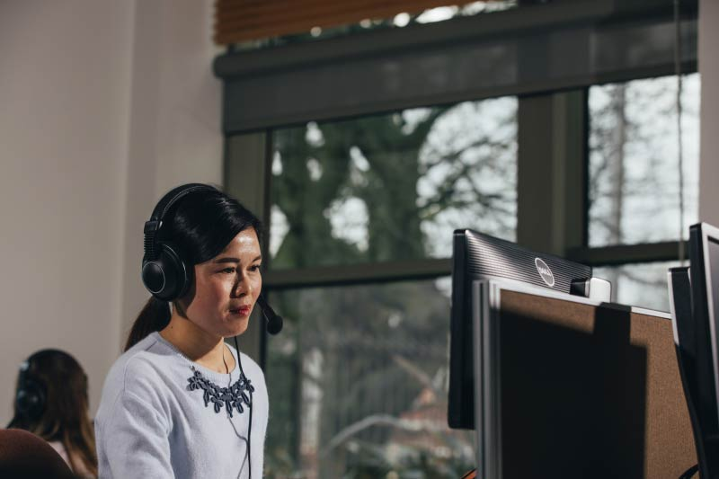 international student using a computer with headphones in the QUB language centre