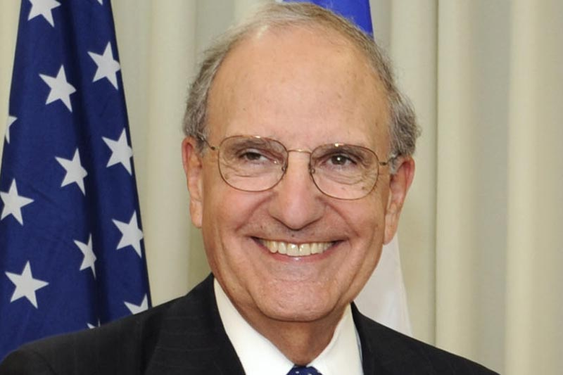 Senator George J. Mitchell smiling in front of the American flag