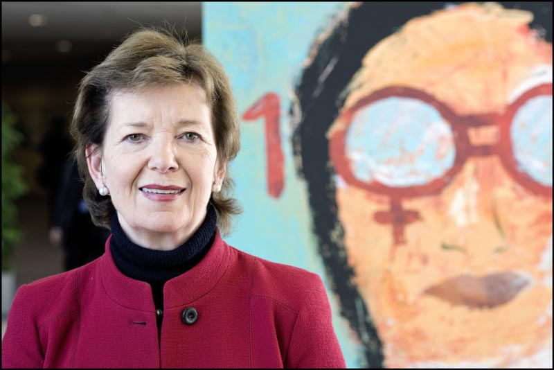 Former President of Ireland, Mary Robinson, standing in front of a colourful mural
