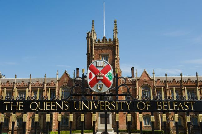 Queen's crest on main gate with Lanyon building in the background