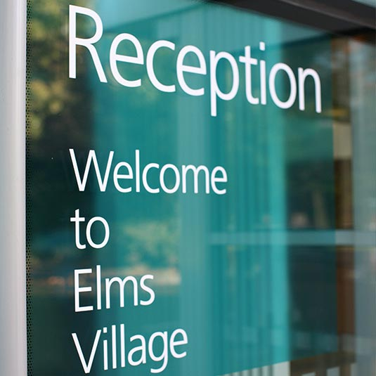 entrance with welcome sign at Elms Village staff office