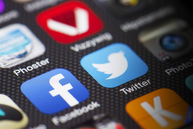 close up of a phone screen with facebook and twitter icons in view