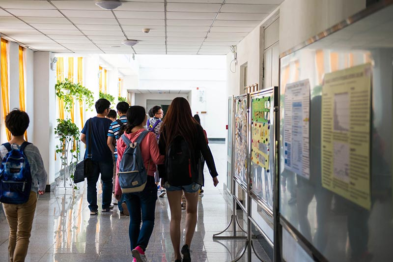 students walking through the hallway of the China Medical University – Queen's Joint College campus