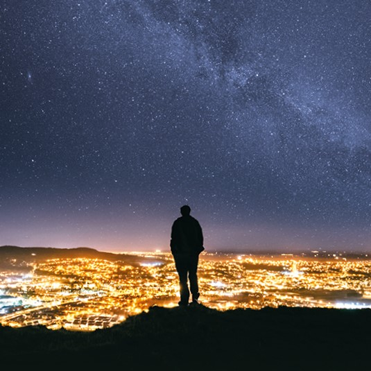 Master plan artwork - silhouette of a man standing on Cave Hill look down on Belfast at night