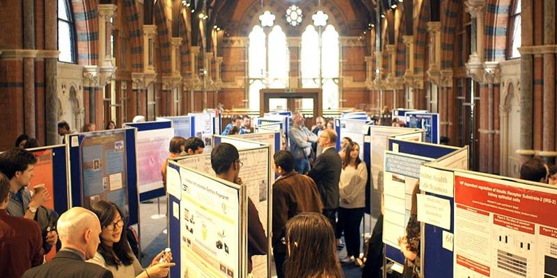 the upper floor of the graduate school filled with posters on boards and students attending a poster competition