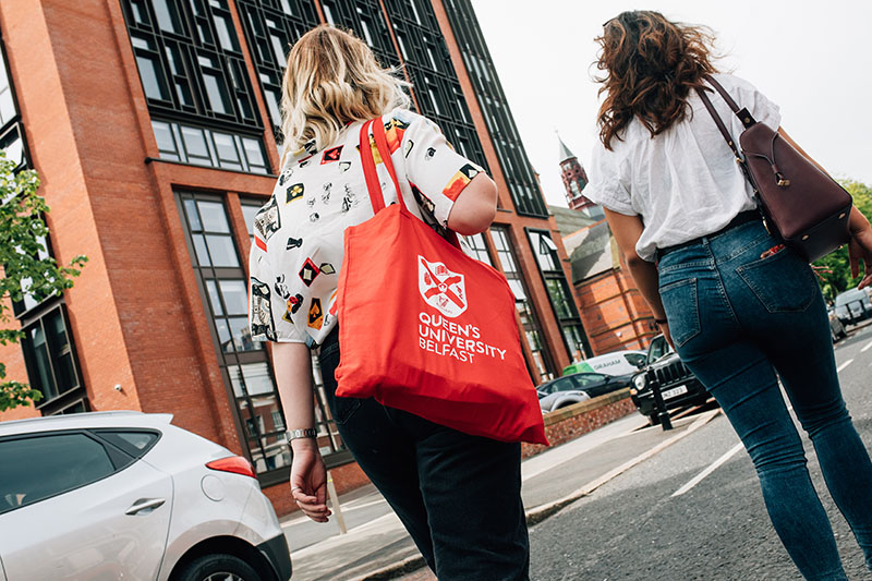 Students walking with a Queen's branded bag