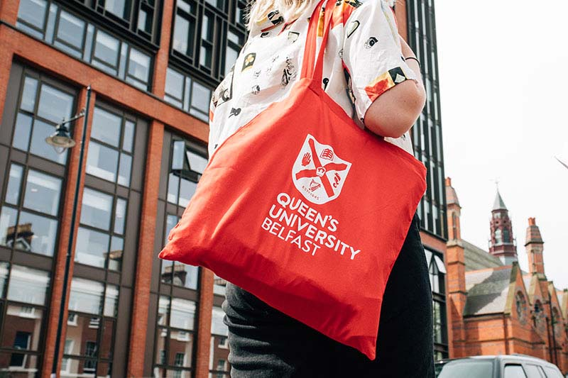 Student carrying a red University branded bag