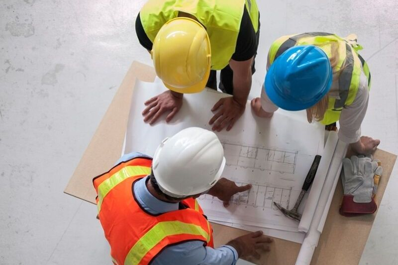 3 people in hard hats look at a plan