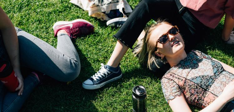 Fresher students relaxing on grass