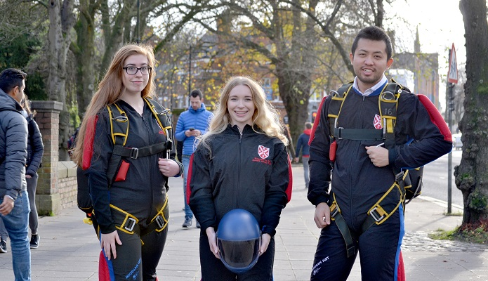 Skydiving club stand together in full suits and helmets